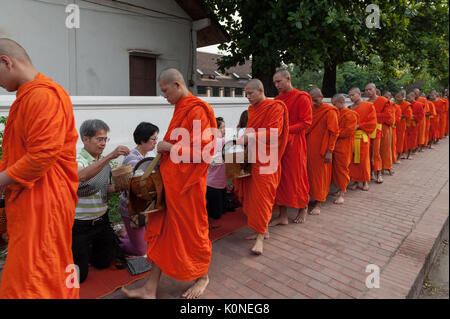 A procession of barefooted monks collects alms along the streets of Luang Prabang, Laos. The most common gifts offered - Stock Photo