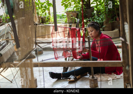 A woman from Xhang Khong village near Luang Prabang operates a spinning wheel to make silk yarn, which will be used - Stock Photo