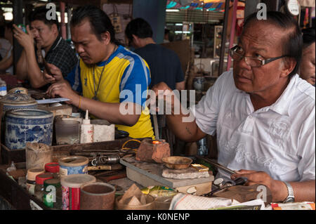 A jewellery maker brazes a ring, one of many repair services provided by goldsmiths at Talat Sao Market in Vientiane. - Stock Photo