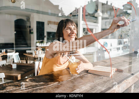 Woman sitting in cafe drawing heart shape on window pane with lipstick - Stock Photo