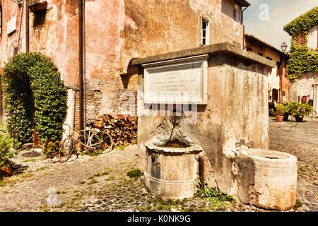 The drinking water fountain in Piazza della Rocca - Medieval Village of Ostia Antica - Rome - Stock Photo