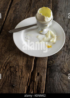 egg shells in an egg-cup  on old wooden weathered table - Stock Photo