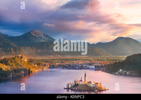 Colorful sunrise over the Bled lake, its surrounding hills, its island and the Karawanks mountains in the background, - Stock Photo