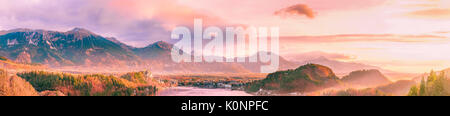 Stunning and colorful panorama with the sunrise shining over the Karawanks mountains, lake Bled and its surrounding - Stock Photo