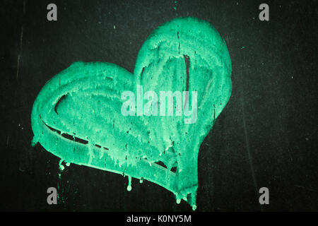 Heart manually painted with drips in green on a scratched blackboard (chalkboard) with imperfect surface - Stock Photo