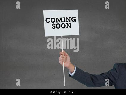 Digital composite of Business man holding a card with coming soon text - Stock Photo