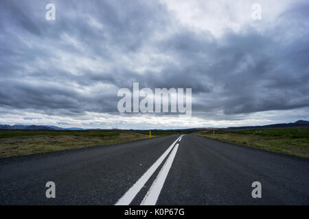 Iceland - Endless street through mountainous landscape and green meadows with cloudy sky - Stock Photo