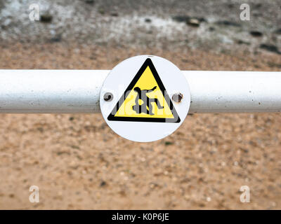 a funny sign on pole indicated a man slipping, slippery surface sea front; England; UK - Stock Photo