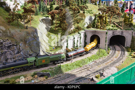 Electric Model Train on miniature train track going through mountain tunnel - Stock Photo