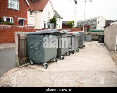 a row of black waste bins outside full; England; UK - Stock Photo