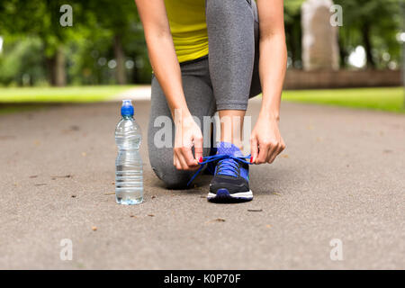 Young woman tying laces of running shoes before training. Healthy lifestyle concept - Stock Photo