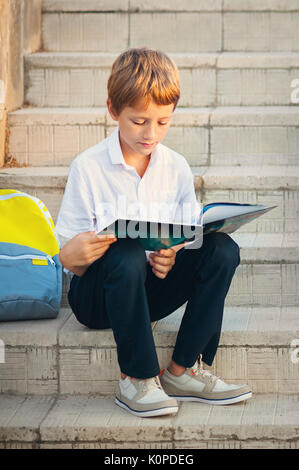 Cute schoolboy studying outdoors on bright autumn day. Boy is reading book with backpack. Back to school. Young - Stock Photo