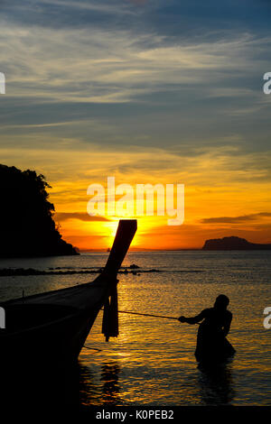 Fisherman pulling fishing boat to go into the sea in early morning. - Stock Photo