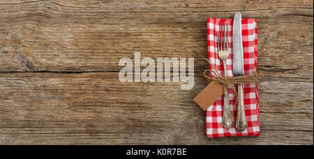 Vintage silverware with an empty tag on wooden background - Stock Photo