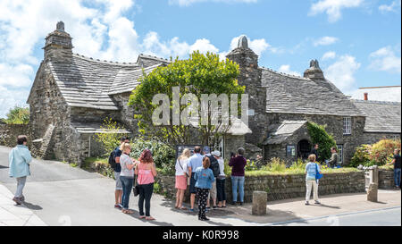 Visitors to the medieval (14th century) Old Post Office, a Grade I listed stone house on Fore Street in Tintagel, - Stock Photo