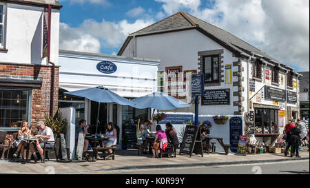 People sitting outside a cafe / restaurant, and others walking along Fore Street, in the small tourist town of Tintagel, - Stock Photo