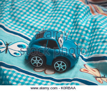 Blue plastic Chinese toy car on a colorful sheet on August 2017 in Poznan, Poland - Stock Photo