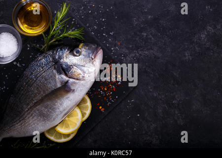 Fresh raw sea bream fish with lemon slices, salt, rosemary and olive oil on black slate background. Healthy food - Stock Photo