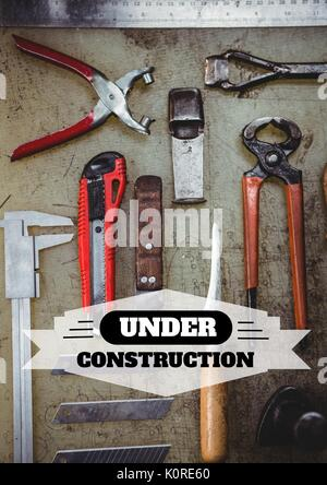 Digital composite of Under construction text against tools photo - Stock Photo