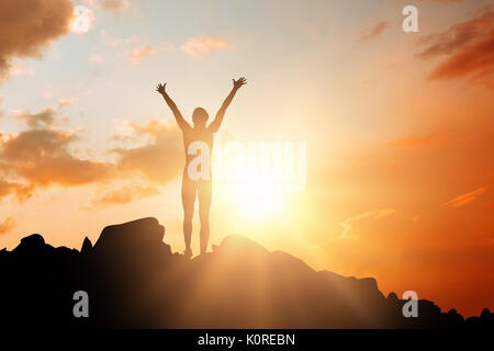 Sportswoman celebrating her victory against orange and blue sky with clouds - Stock Photo