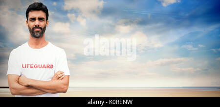 Portrait of male lifeguard with arms crossed against serene beach landscape - Stock Photo