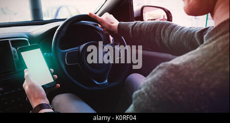 Men looking at GPS on his phone inside his car - Stock Photo