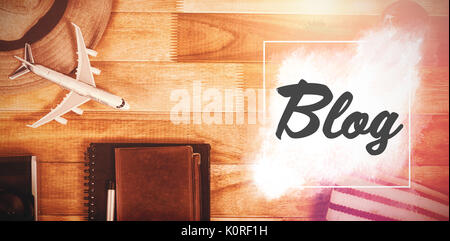 Blog text against white background against overhead view of diary with currency by digital tablet and luggage - Stock Photo