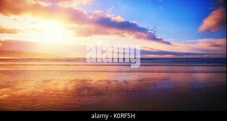 Scenic view of beach against cloudy sky during sunset - Stock Photo