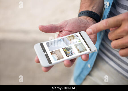 Interior of house on mobile screen against midsection of man using phone - Stock Photo