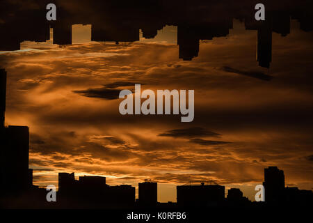 Silhouette buildings in city against cloudy sky during sunset - Stock Photo