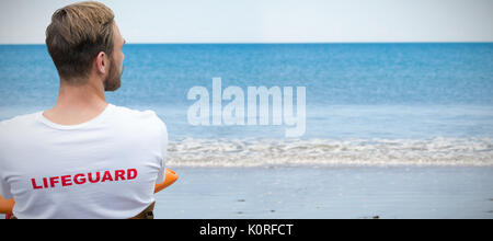 Rear view of male lifeguard against waters edge at the beach - Stock Photo