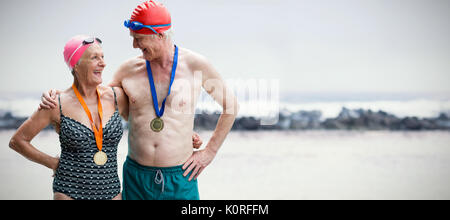 Senior couple in swimwear wearing medals against view of waves - Stock Photo