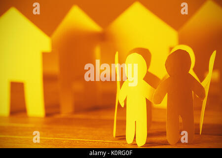 Group of paper figures and houses on wooden table - Stock Photo