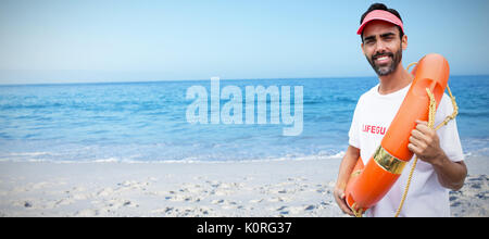 Portrait of male lifeguard holding life belt against beach against clear sky - Stock Photo