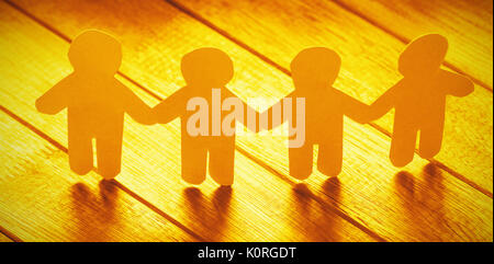 High angle view of white paper cut out figures on wooden table - Stock Photo