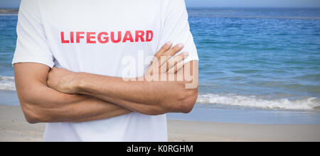 Mid section of male lifeguard against scenic view of beach - Stock Photo