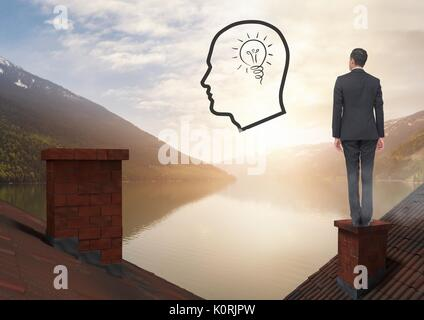 Digital composite of Head and light bulb icon and Businessman standing on Roofs with chimney and lake mountain landscape - Stock Photo
