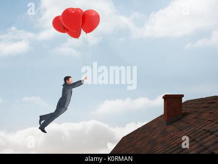 Digital composite of Businessman floating with balloons by Roof with chimney and blue sky - Stock Photo