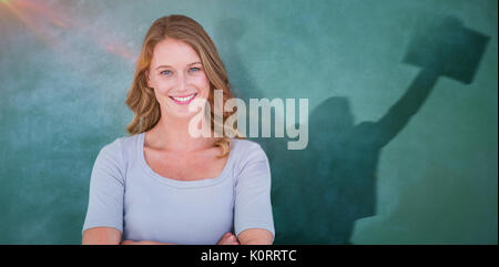 Smiling teacher standing in front of blackboard against businessman jumping while holding briefcase - Stock Photo