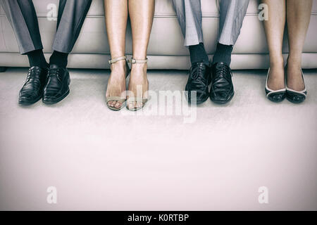 Low section of business people waiting for job interview - Stock Photo