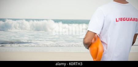 Mid section of male lifeguard with rescue buoy against two starfish kept on sand - Stock Photo