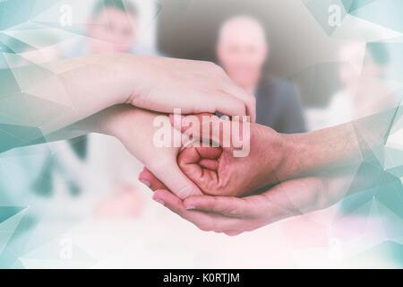 Composite image of cropped hands holding together - Stock Photo