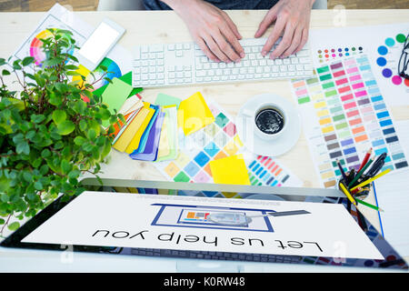 Let us help you text with computer icon against graphic designer working using computer at desk - Stock Photo