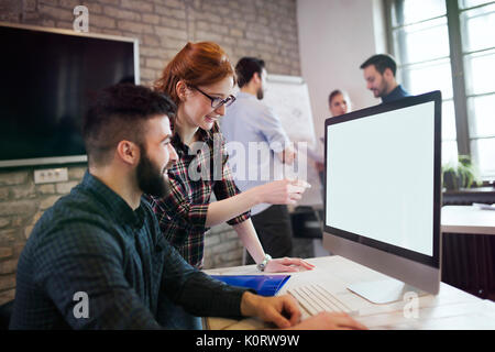 Portrait of young designers working on computer - Stock Photo
