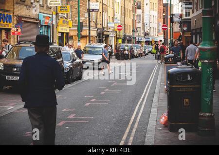 Man walking on Brick Lane in East London (UK). July 2017. Landscape format. - Stock Photo