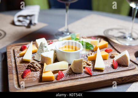 various cheeses with nuts and berries on a wooden Board - Stock Photo
