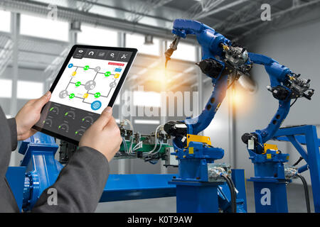 Engineer hand using tablet, heavy automation robot arm machine in smart factory industrial with tablet real time - Stock Photo