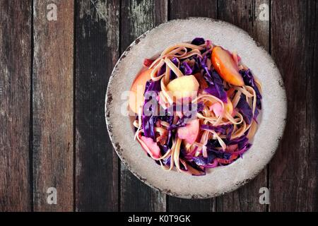 Autumn pasta dish with apples, purple cabbage and bacon, overhead view on rustic wood - Stock Photo