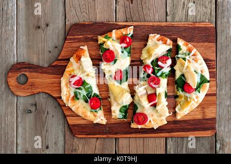 Healthy flat bread pizza with melted mozzarella, tomatoes, spinach and artichokes, above view on wooden paddle board - Stock Photo