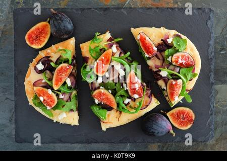 Autumn flat bread pizza with figs, arugula, and goat cheese, overhead scene on slate background - Stock Photo
